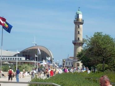 """Blick auf die Warnemünder Promenade mit den Wahrzeichen Leuchtturm und """"Alter Teepot"""""""