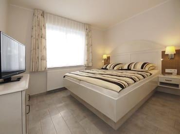 Schlafzimmer mit Doppelbett und 2. Flachbildfernseher