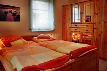 grooßes Schlafzimmer mit Gesundheitsmatratzen, großem Schrank, Spiegel und Fernseher, Blick in Park