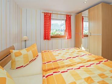 Schlafbereich mit Doppelbett und Schrank.