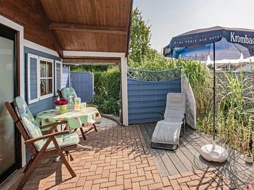Sitzecke mit Sonnenschirm, Liege und Teich.