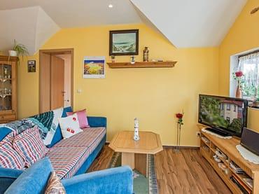 Wohnbereich mit Couch und TV.
