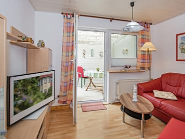 Wohnbereich mit TV und Blick auf die Terrasse.