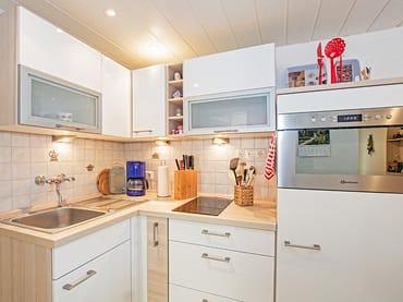 Küche mit Herd und Kaffeemaschine.