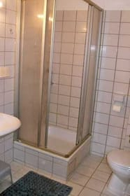 Badezimmer mit Dusche, Waschbecken, WC und Waschmaschine