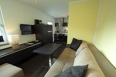 Blick vom Schlafzimmer in den Wohnbereich, mit integrierter Einbauküche