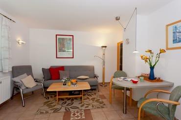 ... mit Esstisch für drei Personen sowie über ein gemütliches Sofa, auf dem Sie nach einem erholsamen Urlaubstag die Seele baumeln lassen können.