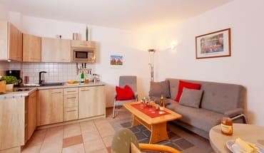 Der Wohnbereich verfügt über eine integrierte moderne Küchenzeile (inkl. Geschirrspüler, Induktionskochfeld etc.) mit Esstisch für drei Personen ...