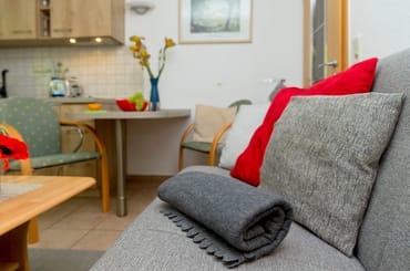 Vom Wohnzimmer erreichen Sie Ihre private Terrasse, die zum Erholen oder zur abendlichen Spielrunde mit Blick in den Garten einlädt.