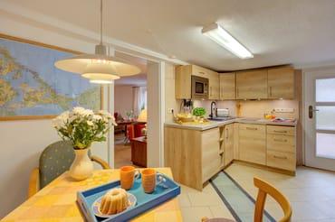 Die separate Küche mit moderner Küchenzeile inkl. Induktionskochfeld, Geschirrspüler, Mikrowelle, Kühlschrank mit Gefrierfach, Wasserkocher, Toaster,...