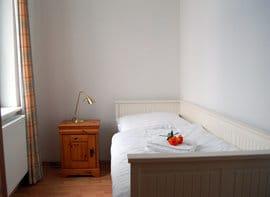 Das zweite Schlafzimmer ist mit einem hochwertigen Einzelbett ausgestattet, das sich bequem zu einem Doppelbett ausziehen lässt.  Das Appartement bietet somit Platz für bis zu vier Personen.