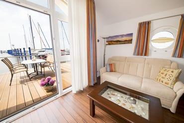 Gemütliche Sitzecke mit Schlafcouch und Blick auf die Terrasse