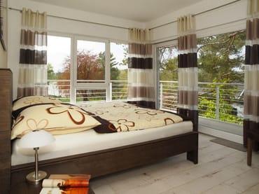 helles großzügiges Schlafzimmer mit Doppelbett