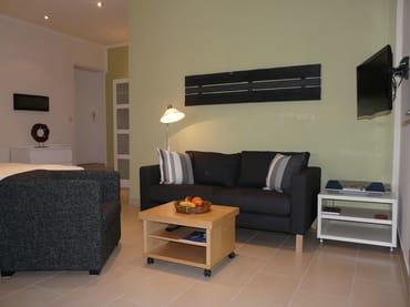 Wohnbereich mit bequemer Couch und gemütlichem Sessel, LCD-TV, Stereoanlage mit Radio/CD