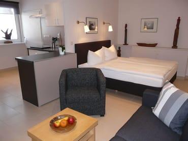 Blick vom Wohnbereich zum Schlafbereich und Küchenbereich
