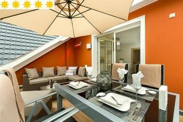 14 qm Süd-Terrasse mit beheizbarer gemütlicher Lounge, großzügigen Esstisch und Sonnenschirm
