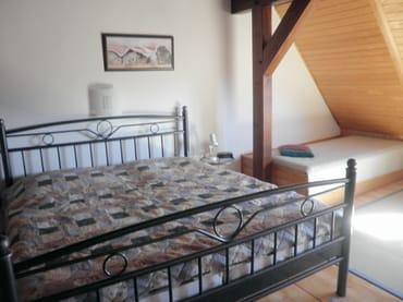 Schlafzimmer mit Doppelbett und zusätzlichem Bett, großer eingebauter Kleiderschrank