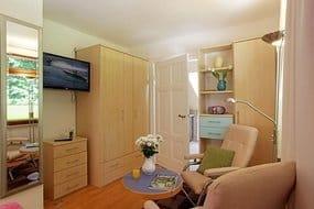 Der kombinierte Wohn- u.Schlafbereich des 23 qm großen Ferienzimmers bietet Ihnen eine Relaxecke mit zwei Polstersesseln u. Flat-TV sowie ein bequemes Doppelbett von dem Sie ebenfalls fernsehen können