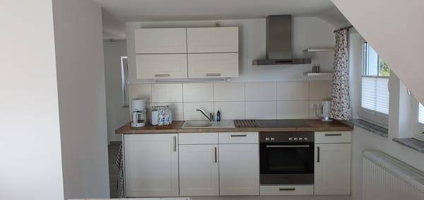 Die Küchenzeile mit  Geschirrspüler, Kühlschrank mit Gefrierfach, Ceranherd und Ablufthaube