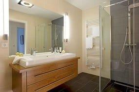 Das Badezimmer ist mit ebenerdiger Echtglas-Dusche, XXL-Waschtisch und WC ausgestattet. Ein Gäste WC mit handbemaltem Waschbecken komplettiert den Urlaubskomfort zu viert.