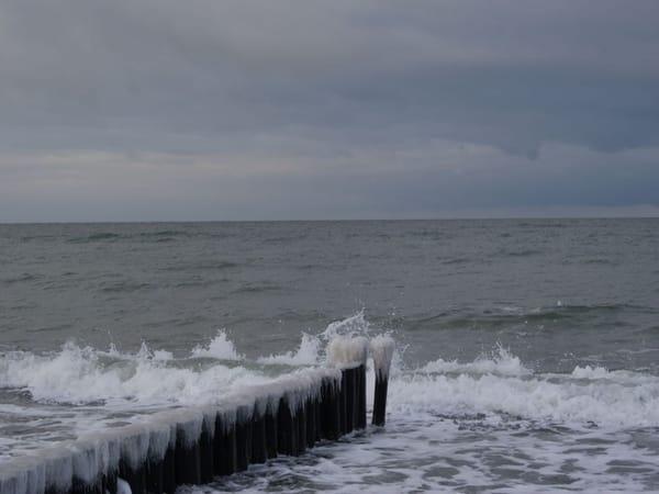 Der Frost versieht die Wellenbreche mit Eismützen