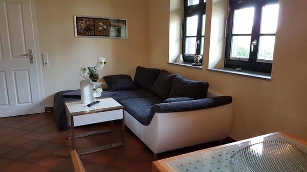 Wohnbeispiel, bequeme Sitzcouch mit Ottomane in unseren Dreiraumwohnungen