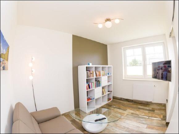 zweiter Wohnbereich mit Couch, TV und Auswahl an Büchern und Spielen