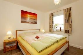 Ein Schlafzimmer mit Doppelbett und Flat-TV...