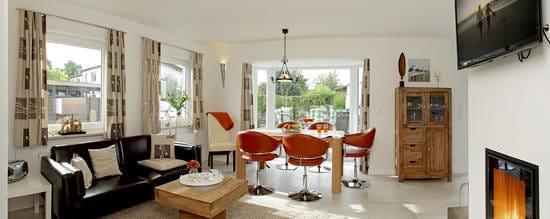 Im Erdgeschoss befindet sich der lichtdurchflutete Wohn- und Essbereich mit gemütlicher Couch, Flat-TV, Kamin und großzügigem Esstisch sowie Zugang zur Südterrasse.