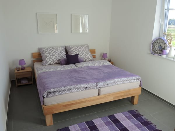 Schlafzimmer mit Doppelbett und Weitblick in freie Natur