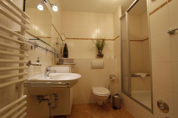Badezimmer mit Sitzmöglichkeit in der Dusche