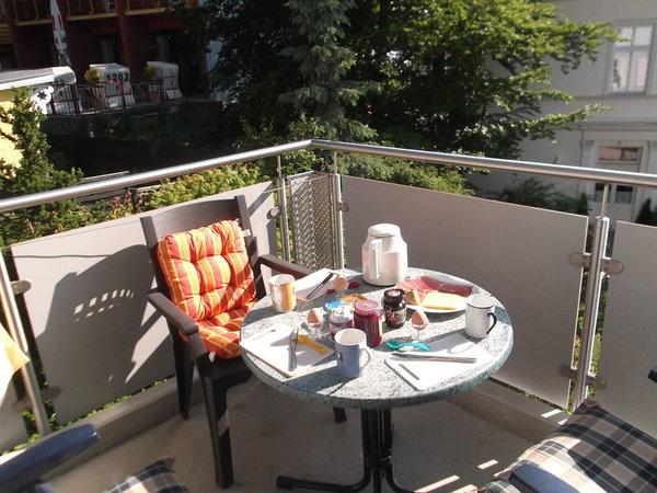 Fühstück bei Morgensonne auf dem Balkon