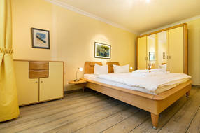 Das Schlafzimmer mit ausreichend Stauraum in einem großen Schrank und einer extra Kommode.