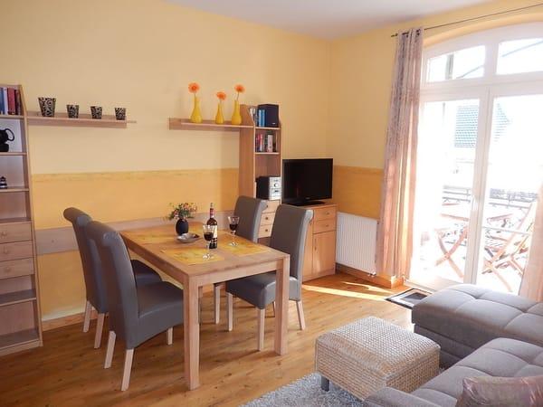 Wohnraum mit LCD-TV, Hifi-System, Sofa-Ecke, Esstisch, Küche u Blick zum Ostbalkon