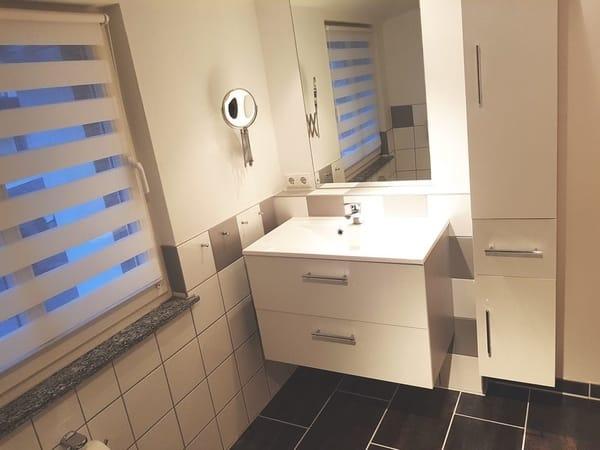 Badezimmer mit Dusche, WC, Handtuchheizkörper, Kosmetikspiegel und Fön