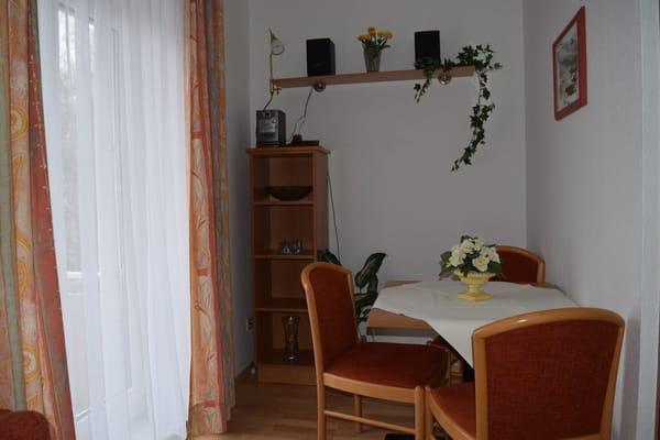 Wohnzimmer mit Blick zur Balkontür und Essecke