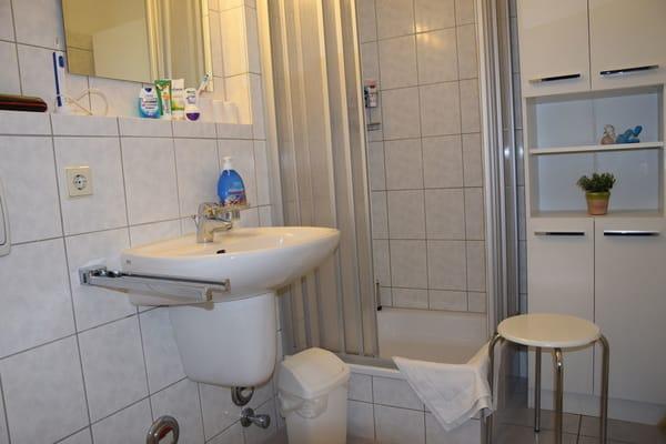Geräumiges, weißes Duschbad mit Ablagemöglichkeiten, zahlreiche Haken für Handtücher und Duschhandtuchstange.usw. .