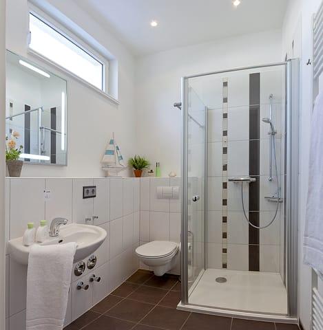 Das moderne Badezimmer ist mit WC, Dusche und einem Haarfön ausgestattet.