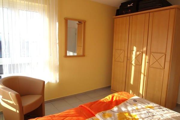 Schlafzimmer im Turm,  mit  Doppelbett, großem  Kleiderschrank, Sessel und Spiegel.