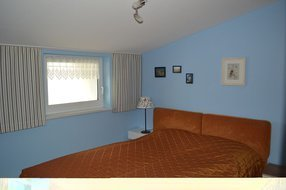 Schlafzimmer mit einem Doppelbett mit einer Liegefläche von 160 cm x 200 cm