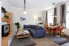 Der angrenzende große Esstisch bietet Platz für bis zu vier Personen.  Auf der Schlafcouch mit Federkernmatratze im Wohnbereich können zwei Gäste Ihr Schlafgemach beziehen.