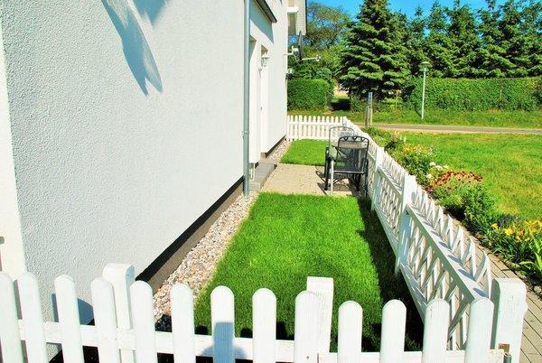 Eingezäunter Vorgarten mit kleiner Terrasse