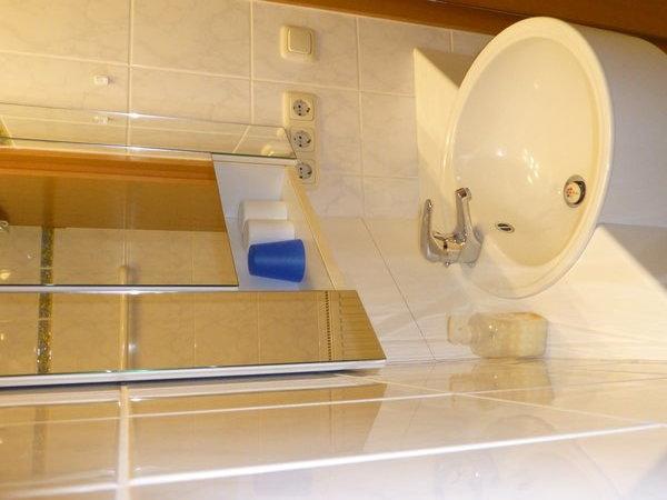 Bad mit Eckwaschtisch und Spiegelschrank.