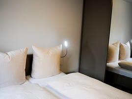 Schlafraum mit Doppelbett, Kleiderschrank und Fenster