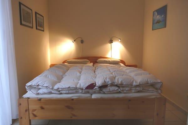 Schlafzimmer mit Doppelbett, Schrank, Korbstuhl, Spiegel
