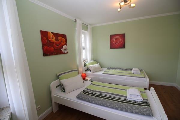 Grünes Schlafzimmer mit 2 Doppelbetten