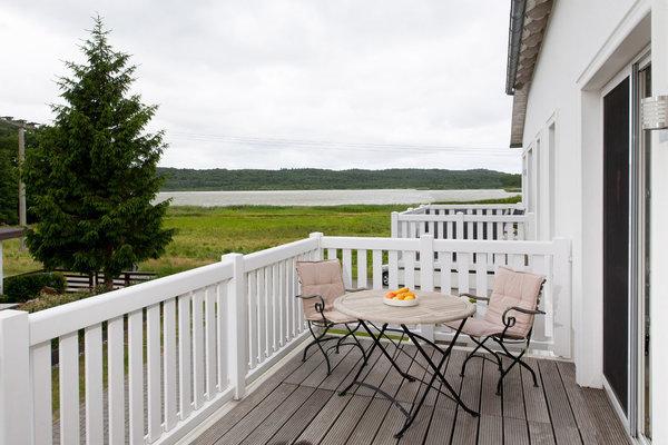 Südwestbalkon mit Teakholztisch- und Stühlen, Sonnenschirm und Outdoorsesseln