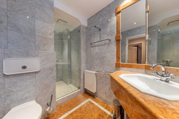 Das edle Bad ist marmorgefliest und hat eine Echtglasdusche.