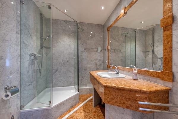 Das marmorgeflieste Bad hat Dusche, WC und Fön.