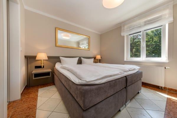 Das Schlafzimmer mit Doppelbett. Das Fenster hat Verdunkelungsplissees.